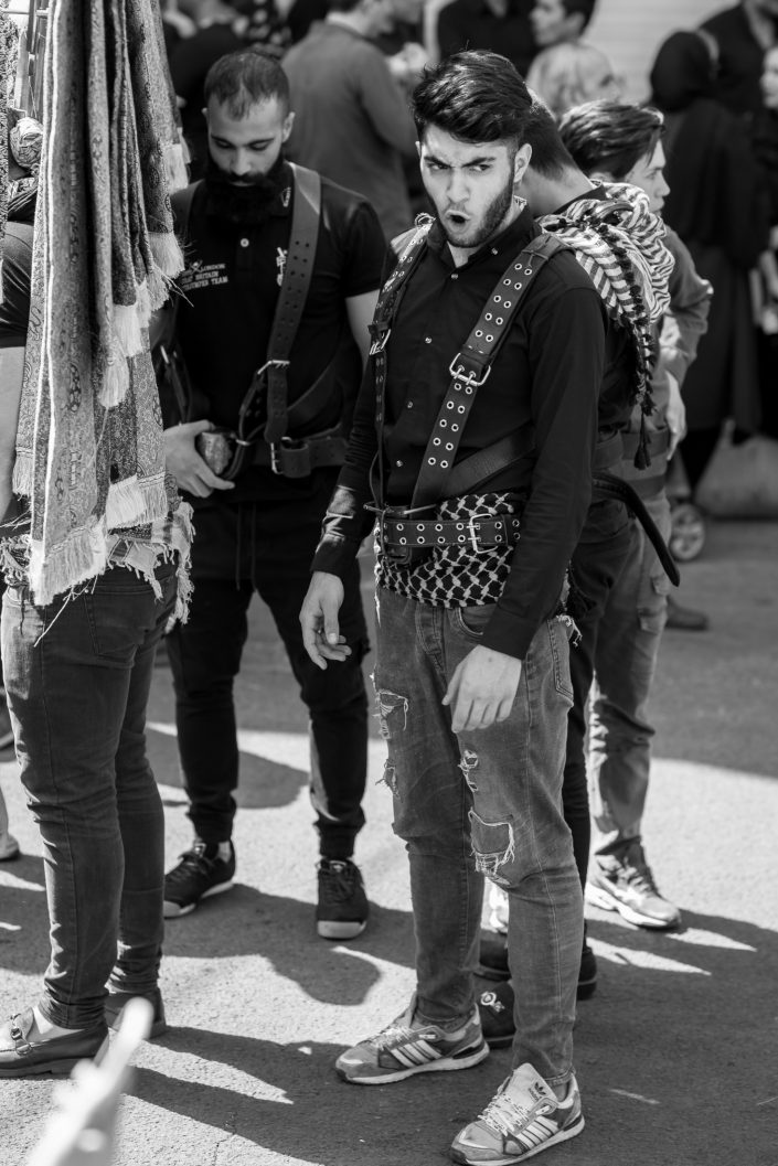Men dressed for Ashura stands with others