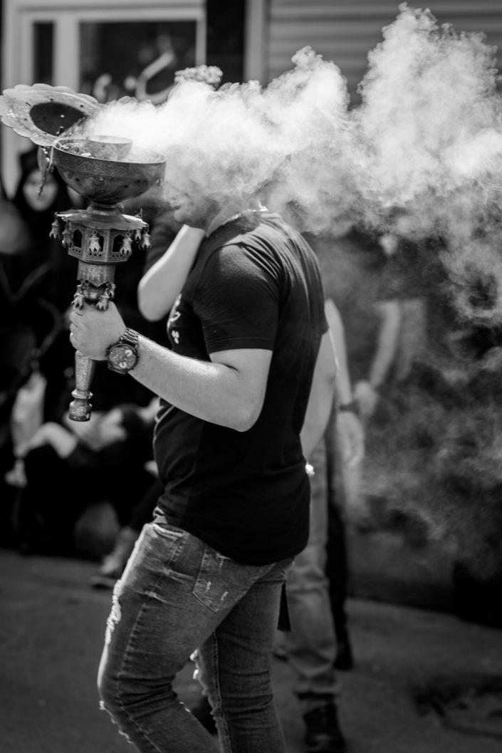 Men holding a smoky incense burner, Ashura, Iran