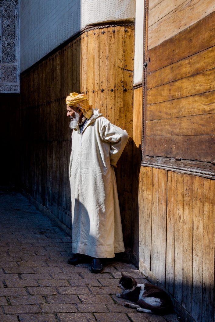 Morrocan elder wearing kaftan at his doorway, cat laying nearby