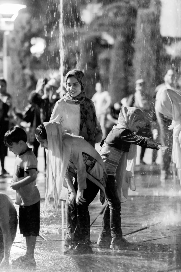 Children wet at night playing with water, Tehran