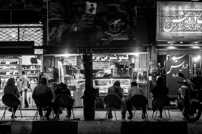 Tehran by night, group of people sitting front of shop
