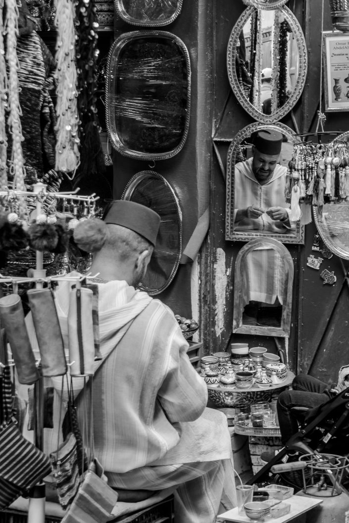 Fez merchant reflected in mirror, Morocco