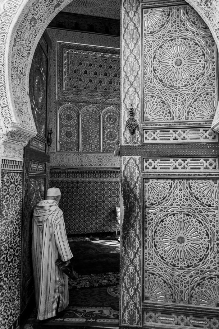 Old man wearing kaftan entering mosque, Fez