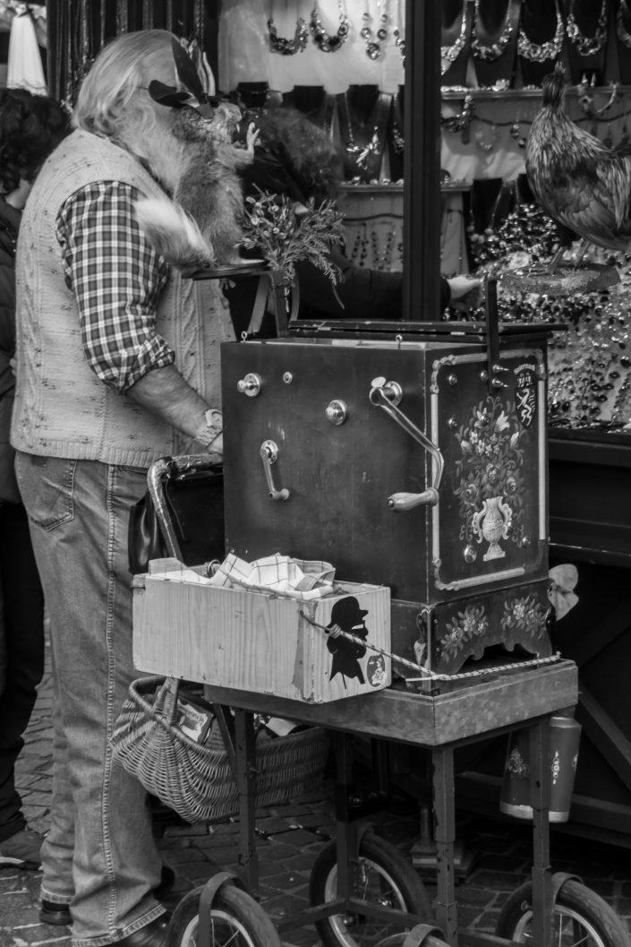 Toy squirrel hiding men's face, market, Austria