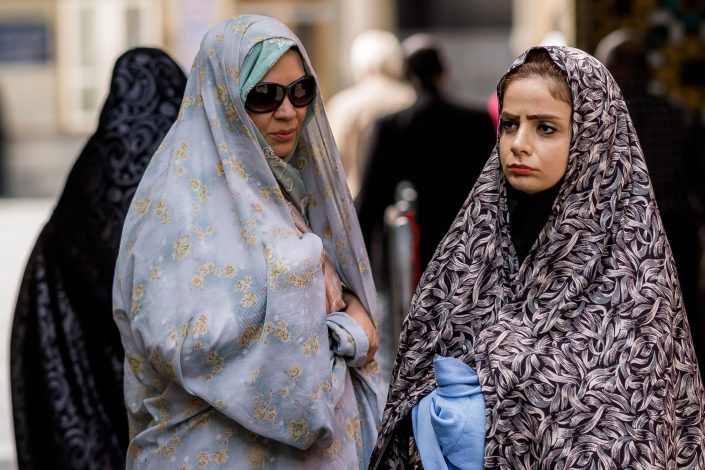 Mother and teenage daughter wearing chadors outside a mosque, Iran