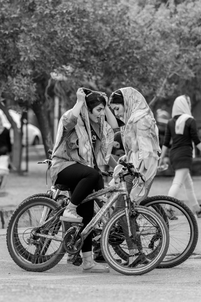 Two young fashionable women riding bicycles, Iran