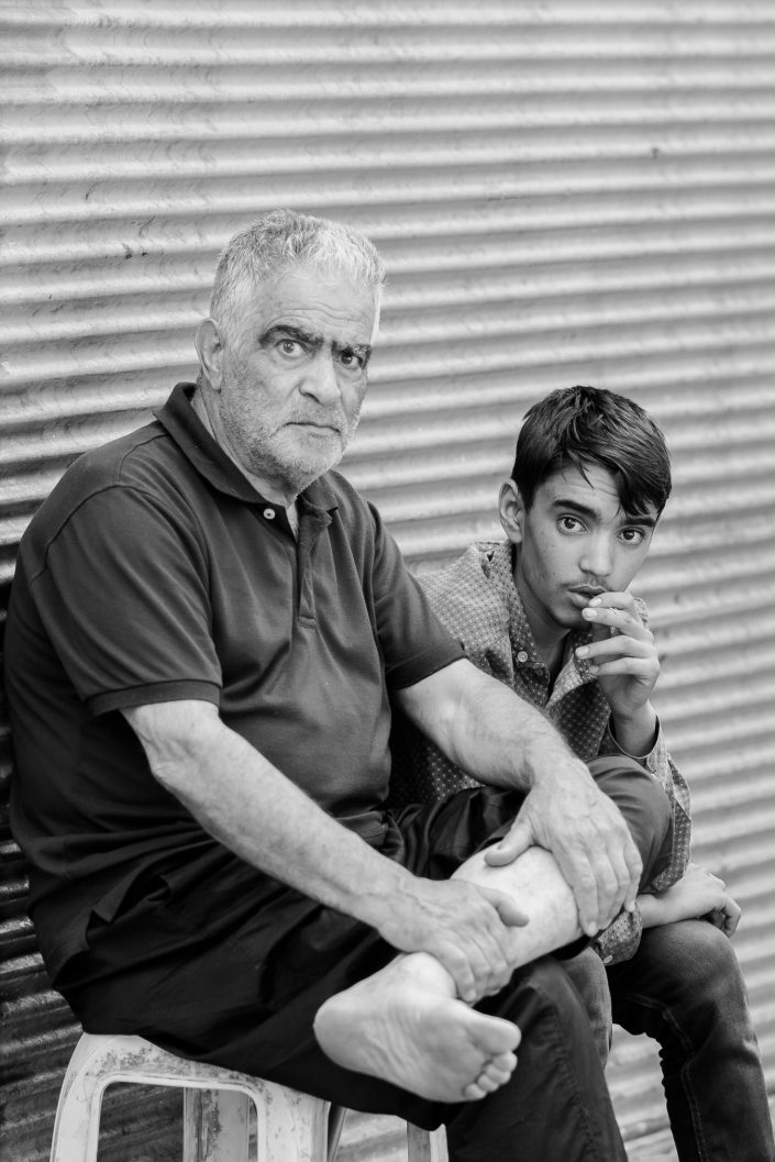 Grandfather and grandson sitting outside their shop, Iran