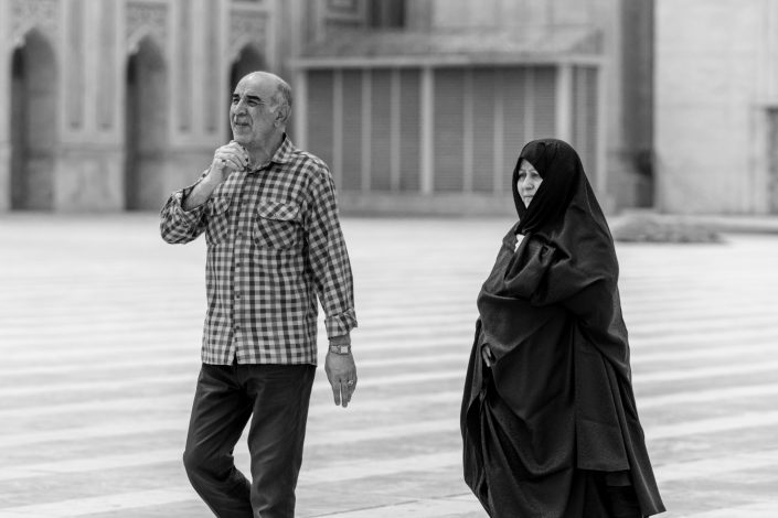 Couple, woman in long chador outside shrine, Iran