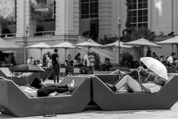 Two couples sleeping holding umbrellas to block sun, Vienna, Austria