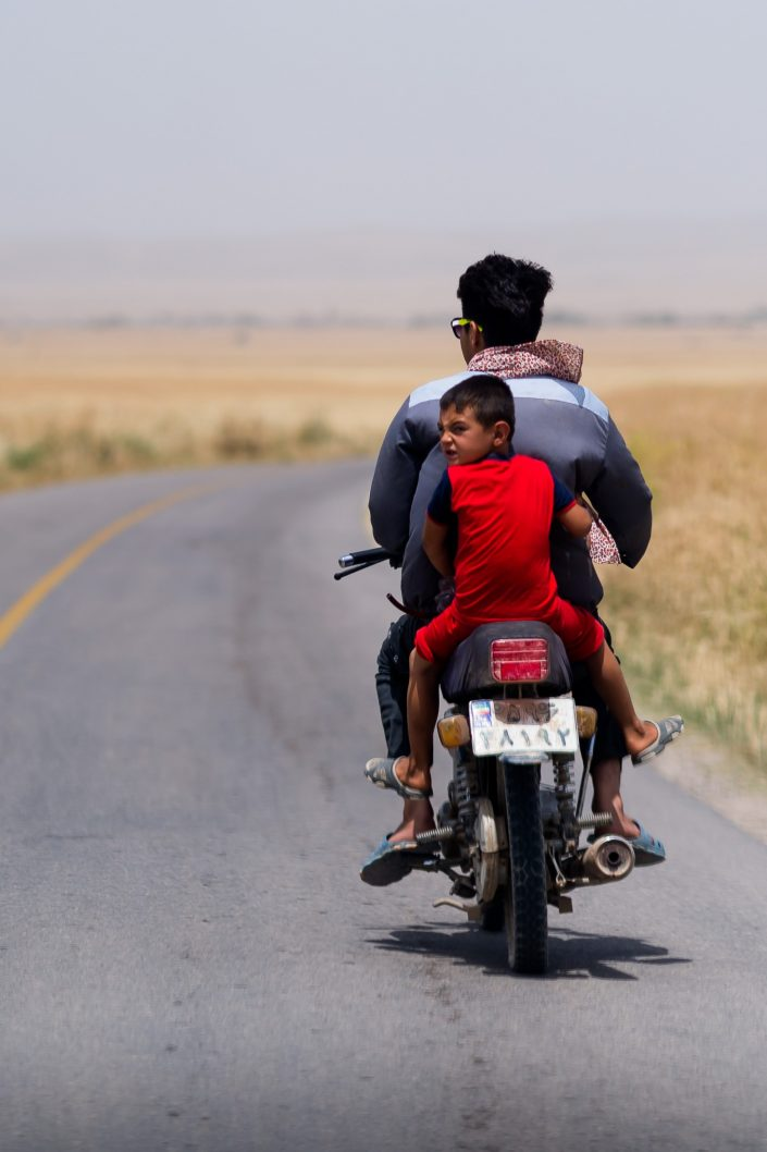 Child riding on the back of a motorbike without a helmet, Iran