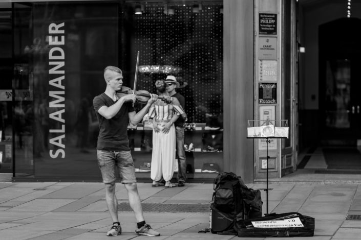 Street musician playing violin, couple background hugging