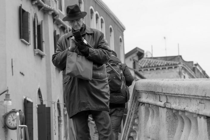 Old man crossing bridge in Venice, Italy