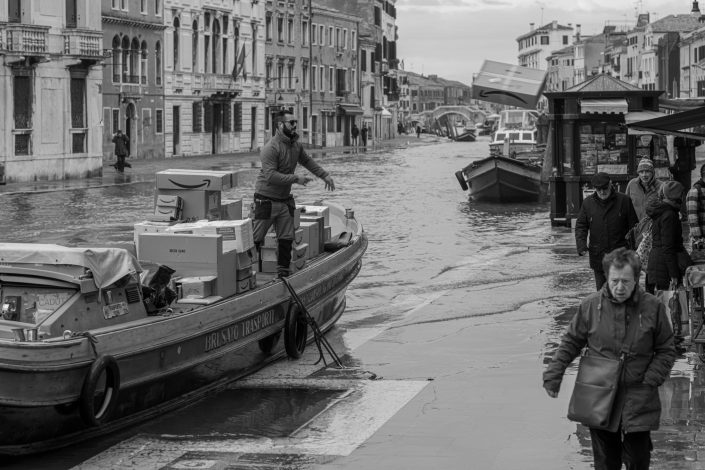 Venice Man throwing package from boat