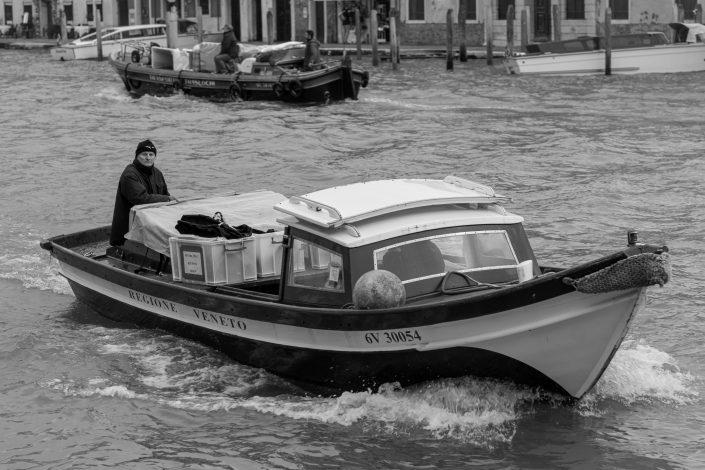 Venice Men driving boat transporting boxes for delivery