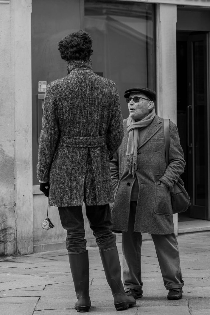 A short man talking to a very tall person in Venice