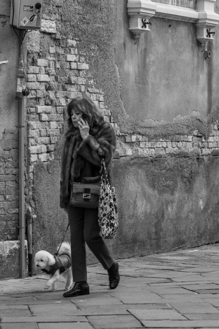 Woman walking dog in Venice, Italy